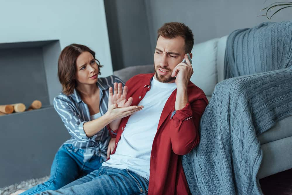 man on cell phone pushing away and ignoring woman next to him. they it on a grey couch with grey decor background