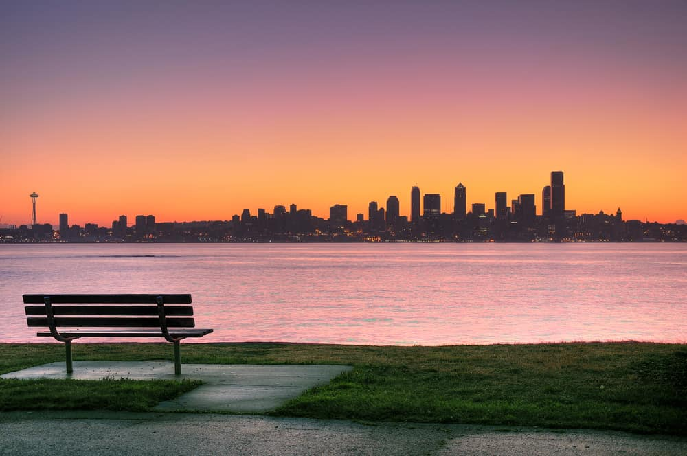 romantic things to do in seattle header image - Sunrise over Emerald city Seattle, park bench in the foreground
