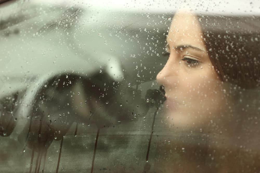 ad woman or teenager girl looking through a steamy car window - relationship red flags header image