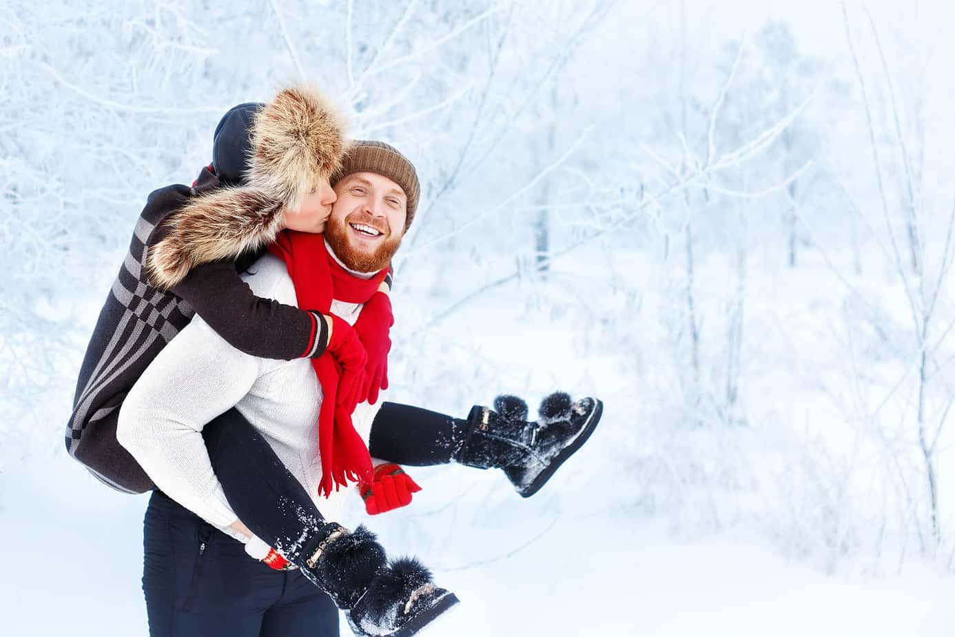 loving texts for him header image - Happy winter couple. Man giving woman piggyback ride on winter vacation in snowy forest. Winter fun couple playful together outdoor. Valentine's Day and love concept. Girl kisses man in winter forest