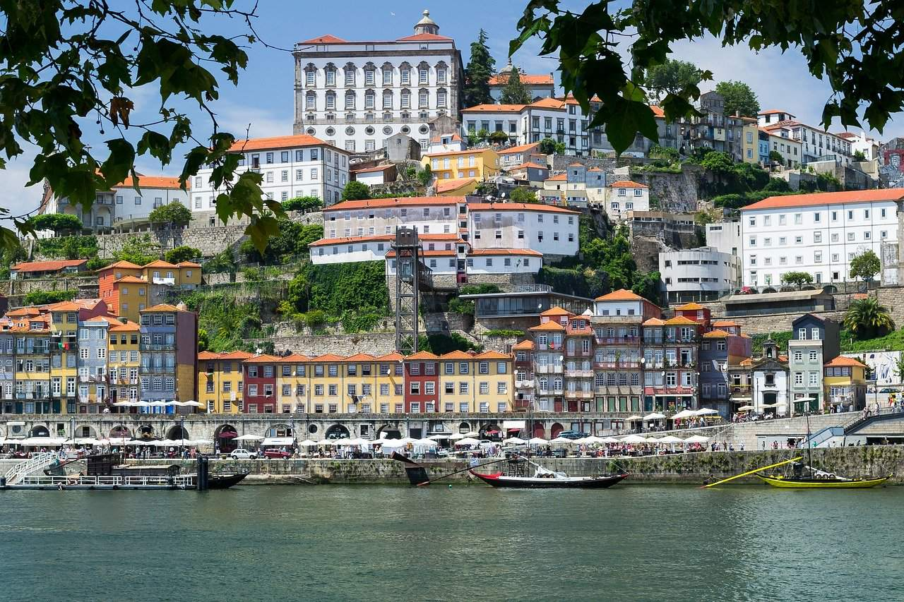 romantic things to do in porto header - image of porto portugal from the water, red tiled buildings on a hill