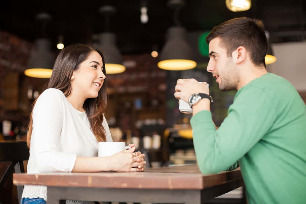 flirty questions to ask a guy - Attractive young couple hanging out and talking while enjoying a cup of coffee at a restaurant