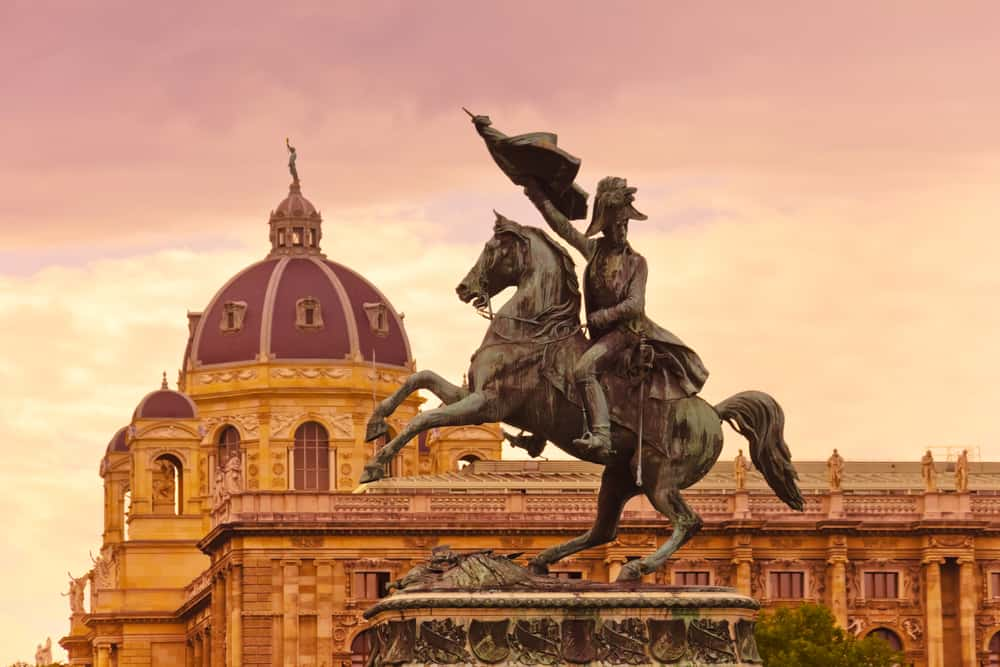 romantic things to do in vienna - statue of horse and rider against church dome at sunset