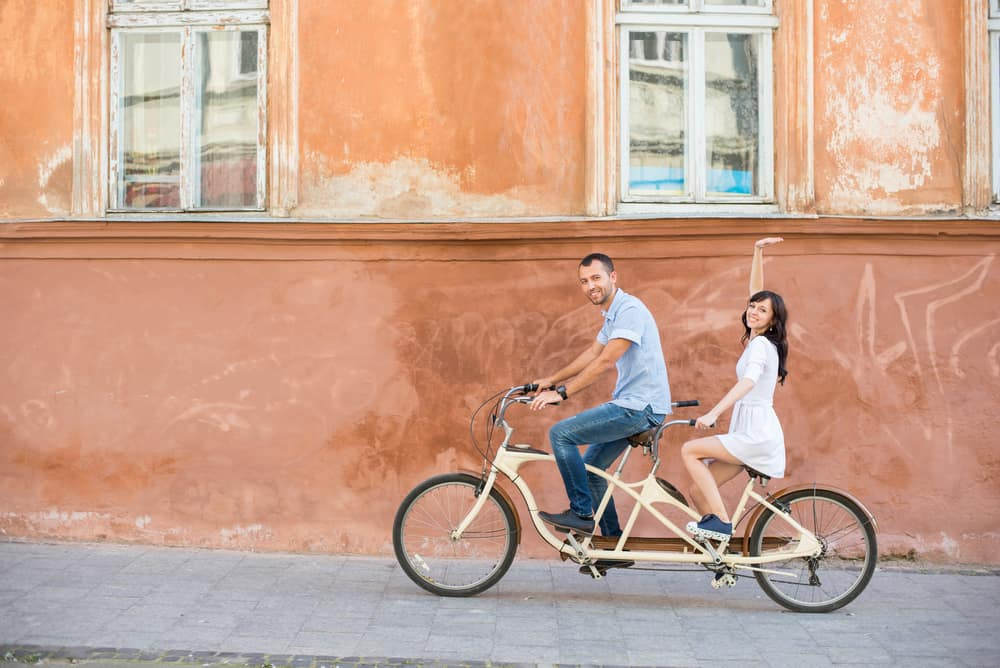 Happy couple riding on retro tandem bicycle at the street city against the background of the old orange wall with windows. The man runs a bicycle, a girl in white dress raised her hand up. Lviv
