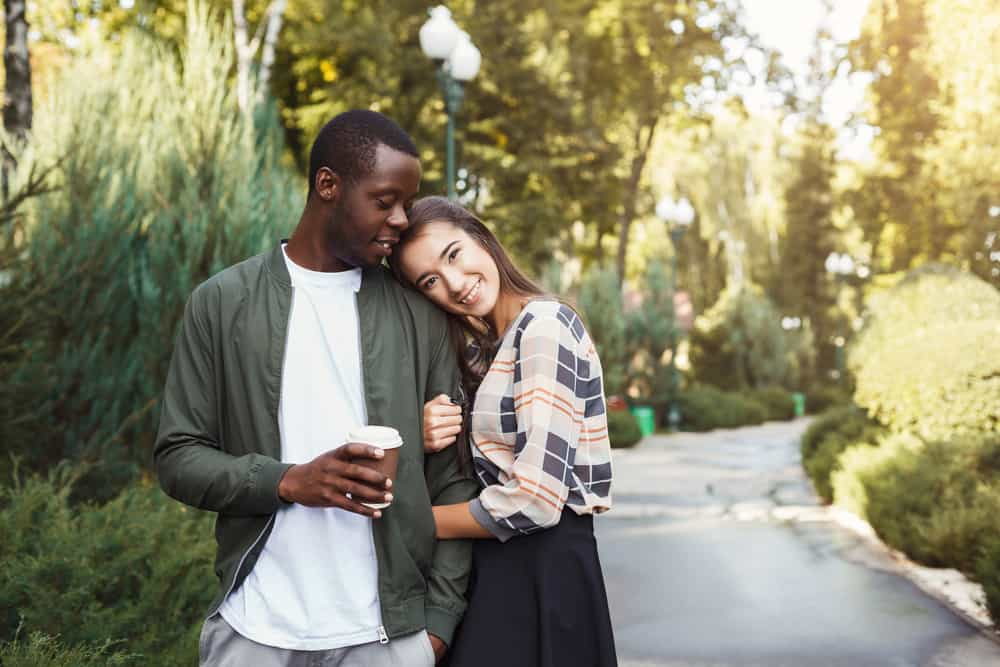 Portrait of happy multiracial couple hugging in park in sunny day, copy space. Love story, romantic date