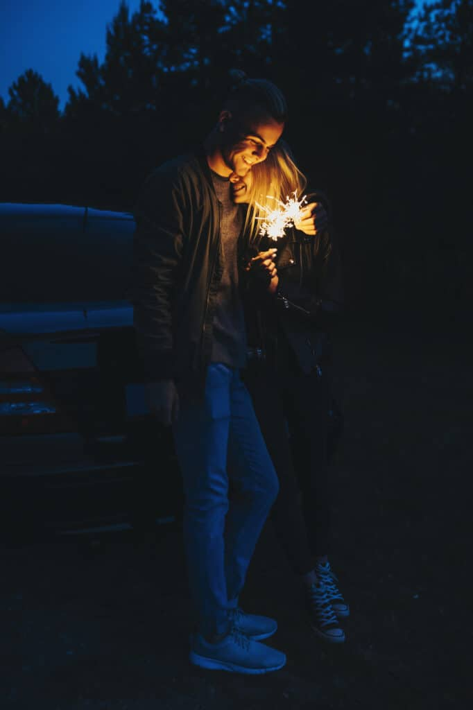 Full length portrait of a lovely couple leaning on their car in the night while embracing and having fun with sparkles.