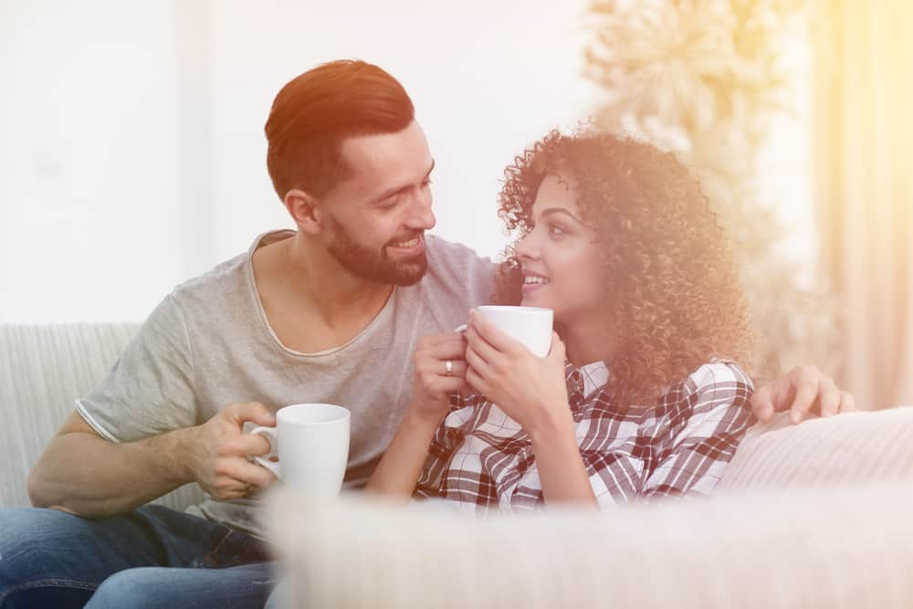 at home date night ideas - loving couple sitting on a sofa in the living room