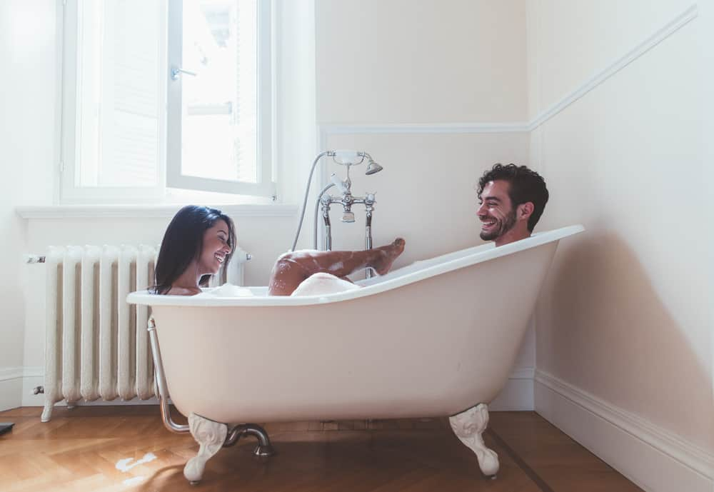 getting through hard times together - couple in the bathtub together at opposite ends