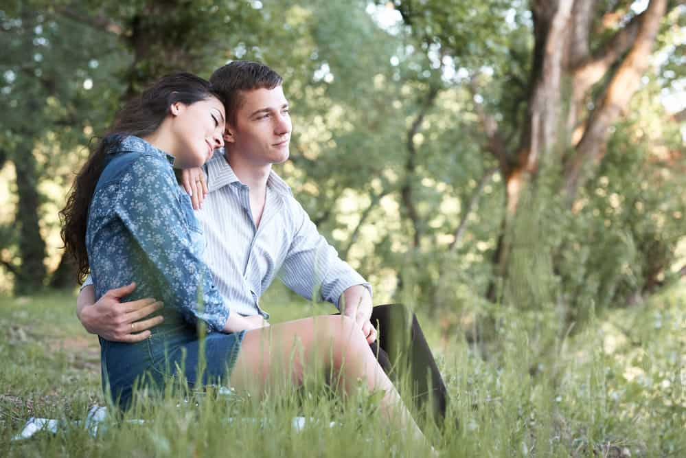 young couple sitting on the grass in the forest and looking on sunset, summer nature, bright sunlight, shadows and green leaves, romantic feelings