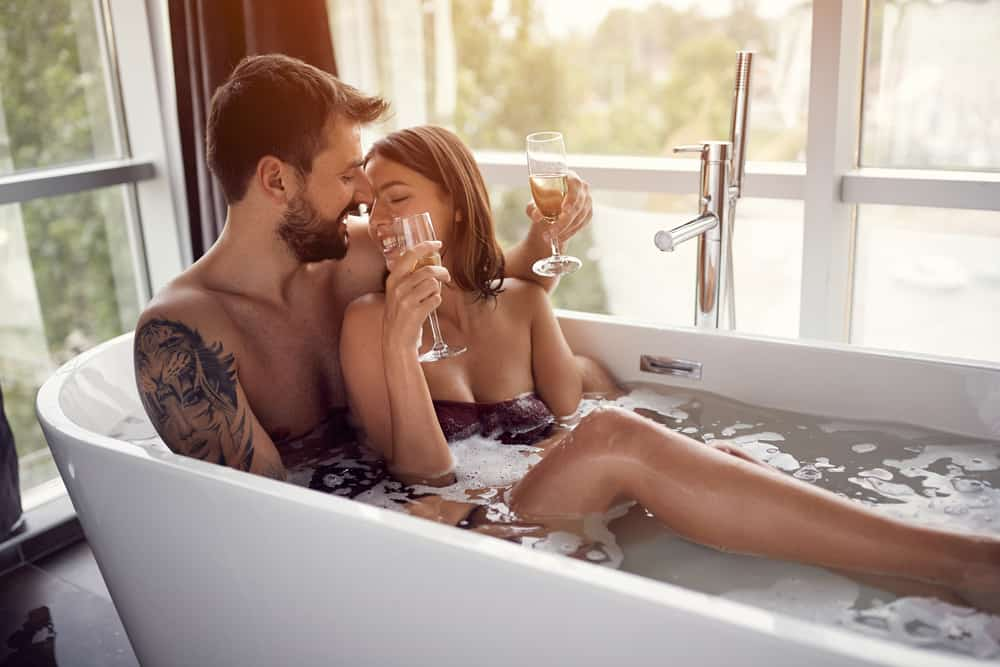 couple in bubble bath together sipping on champagne