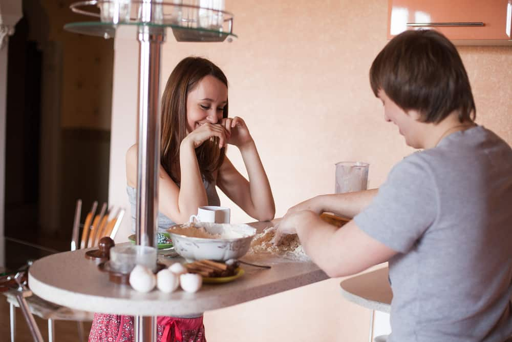 cooking date idea - young happy couple cooking in kitchen