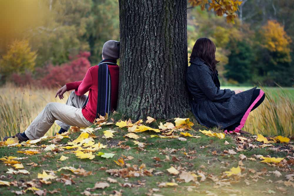 anxiety in relationships - Couple after arguing sitting in autumn park with their backs against either side of a tree trunk