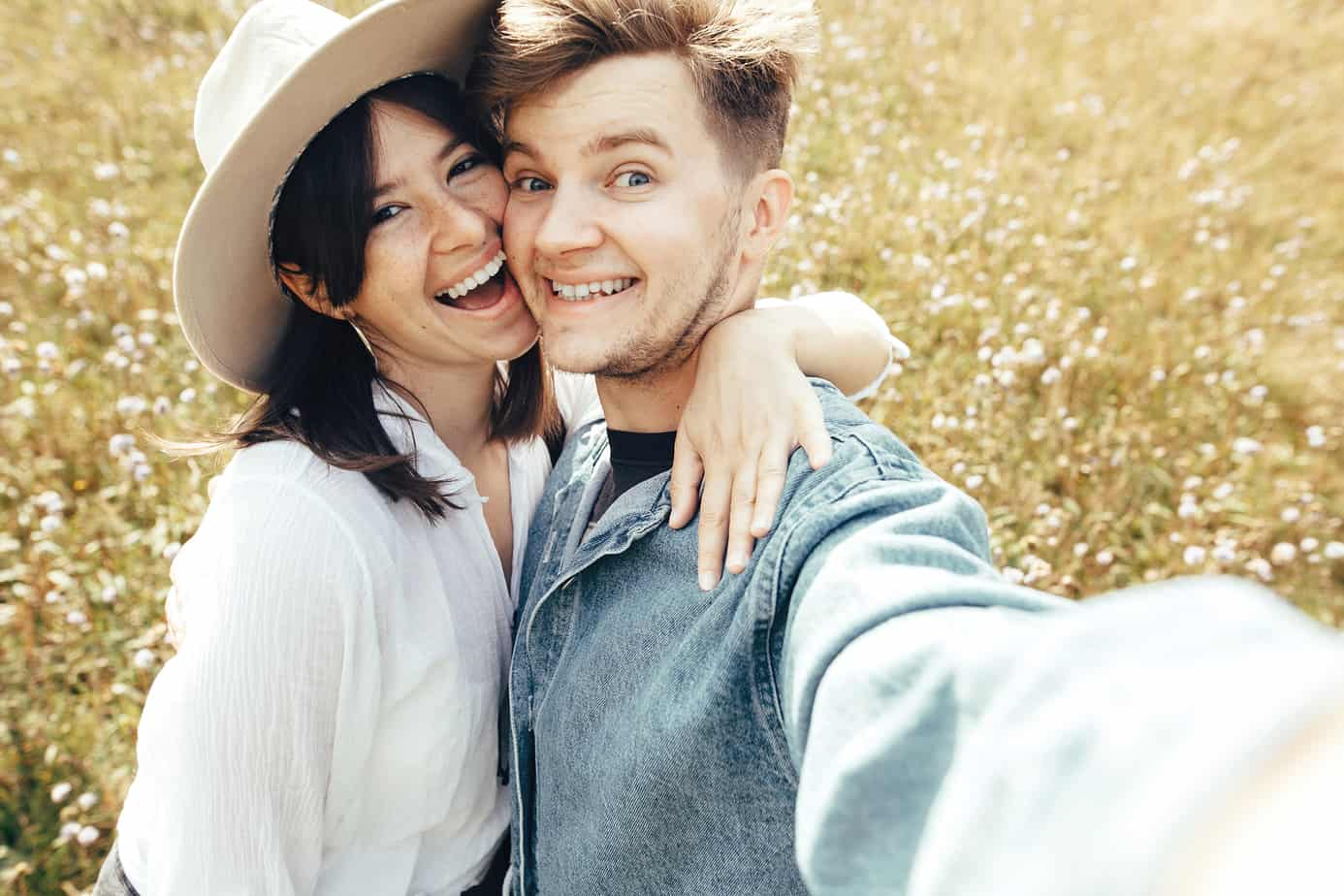 friendship in marriage - Happy hipster couple making selfie in sunny wildflower meadow, traveling in mountains. Stylish young family smiling and enjoying hiking on top of mountain, taking photo. Summer vacation