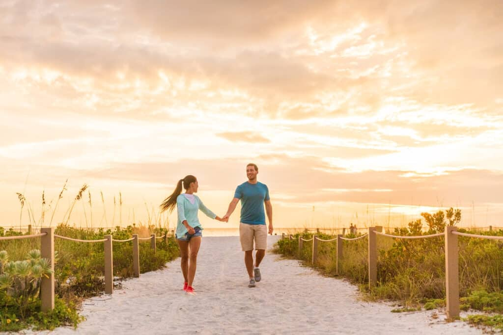 Happy young couple in love walking on romantic beach stroll at sunset. Lovers holding hands on Florida vacation holidays. People walking on summer evening lifestyle