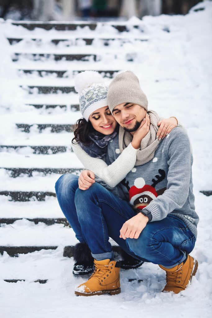 man and girl in sweaters hugging in the park in winter. young couple in love having fun on a winter walk