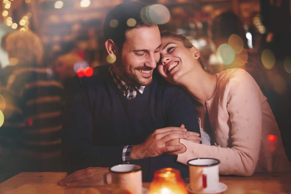 what a husband needs from his wife header image - couple sitting together smiling and laughing in cozy restaurant