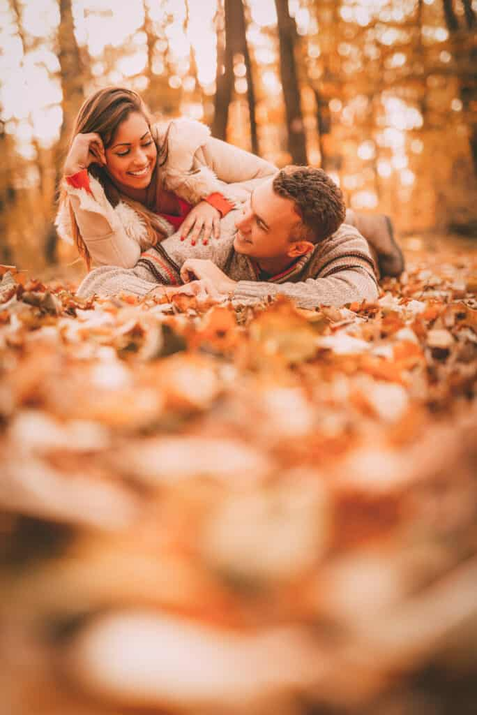 Beautiful smiling couple enjoying in sunny forest in autumn colors. They are lying on the falls leaves and having fun.