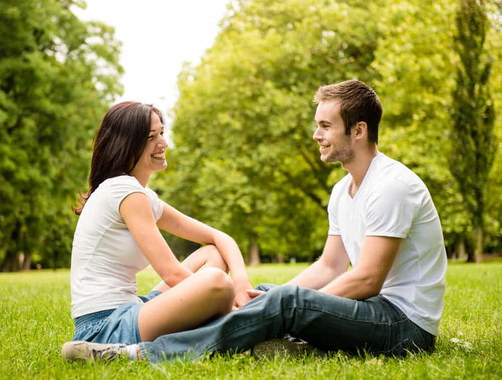 couples communication exercises - Young happy couple talking together outdoor - sitting on grass