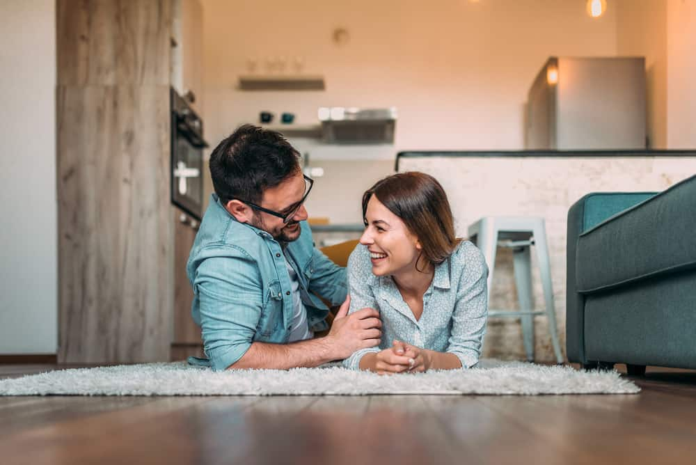 best date night subscription boxes - Laughing while lying on the floor. Couple having a good time at home