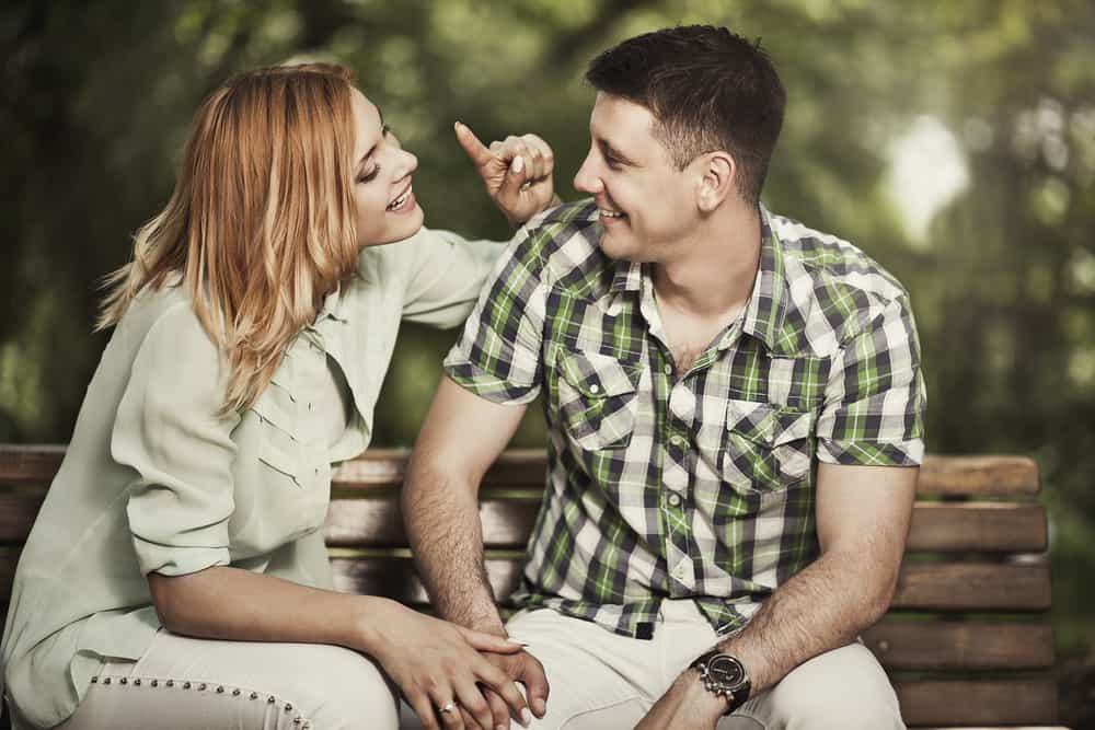 Love and frienship concept. Cheerful couple talking and smiling outdoors.