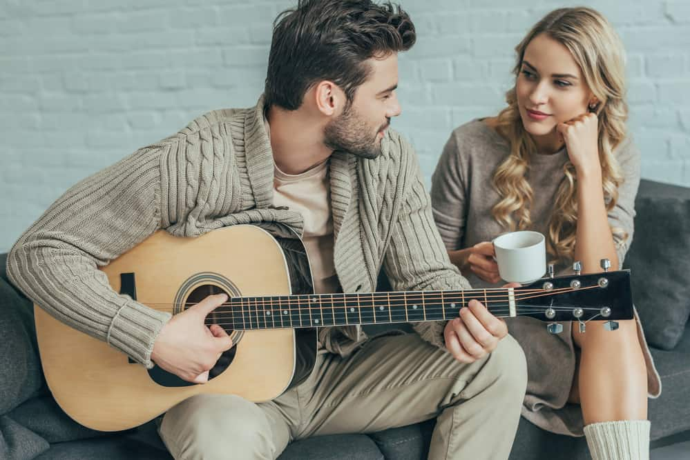 relationship check-in - couple sitting on couch, man playing guitar