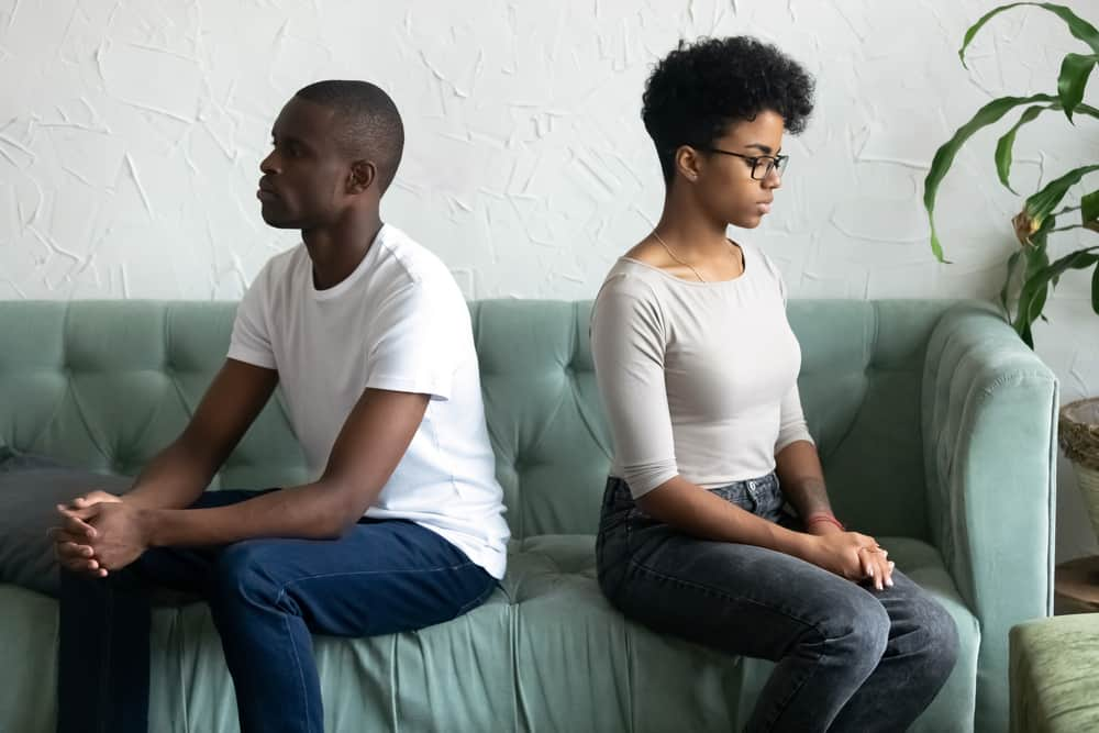 Offended mixed race female sitting apart of sad black man. Spouses after quarrel sitting on couch couple not talking and looking at each other. Break up betrayal and problems in relationships concept