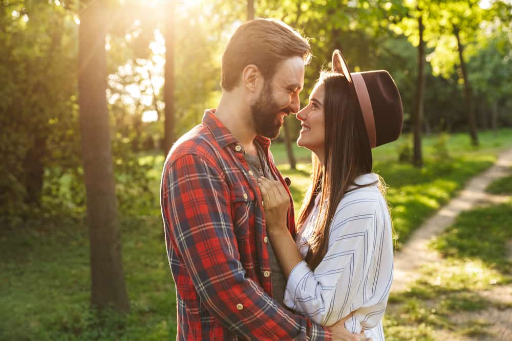 Image of a cheerful pleased romantic young loving couple walking outdoors in a green nature park forest kissing.