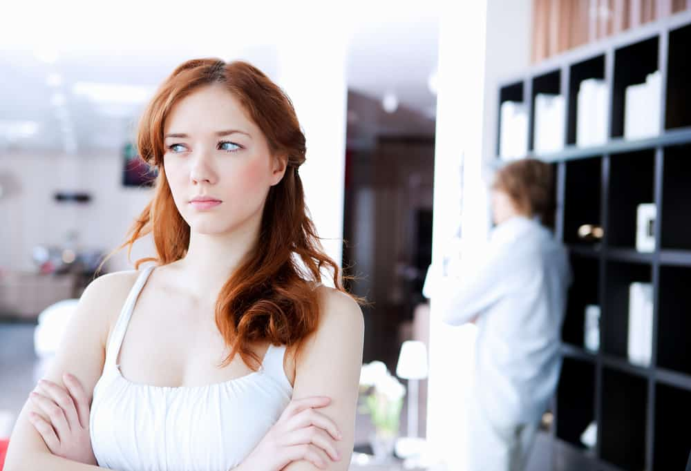 marriage mistakes - picture of couple in disagreement at home in the living room