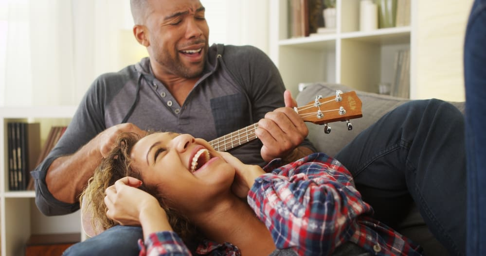 best things about being married - Happy black couple lying on couch with ukulele