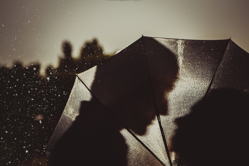 most romantic movies of all time - black and white silhouette of couple close together behind umbrella