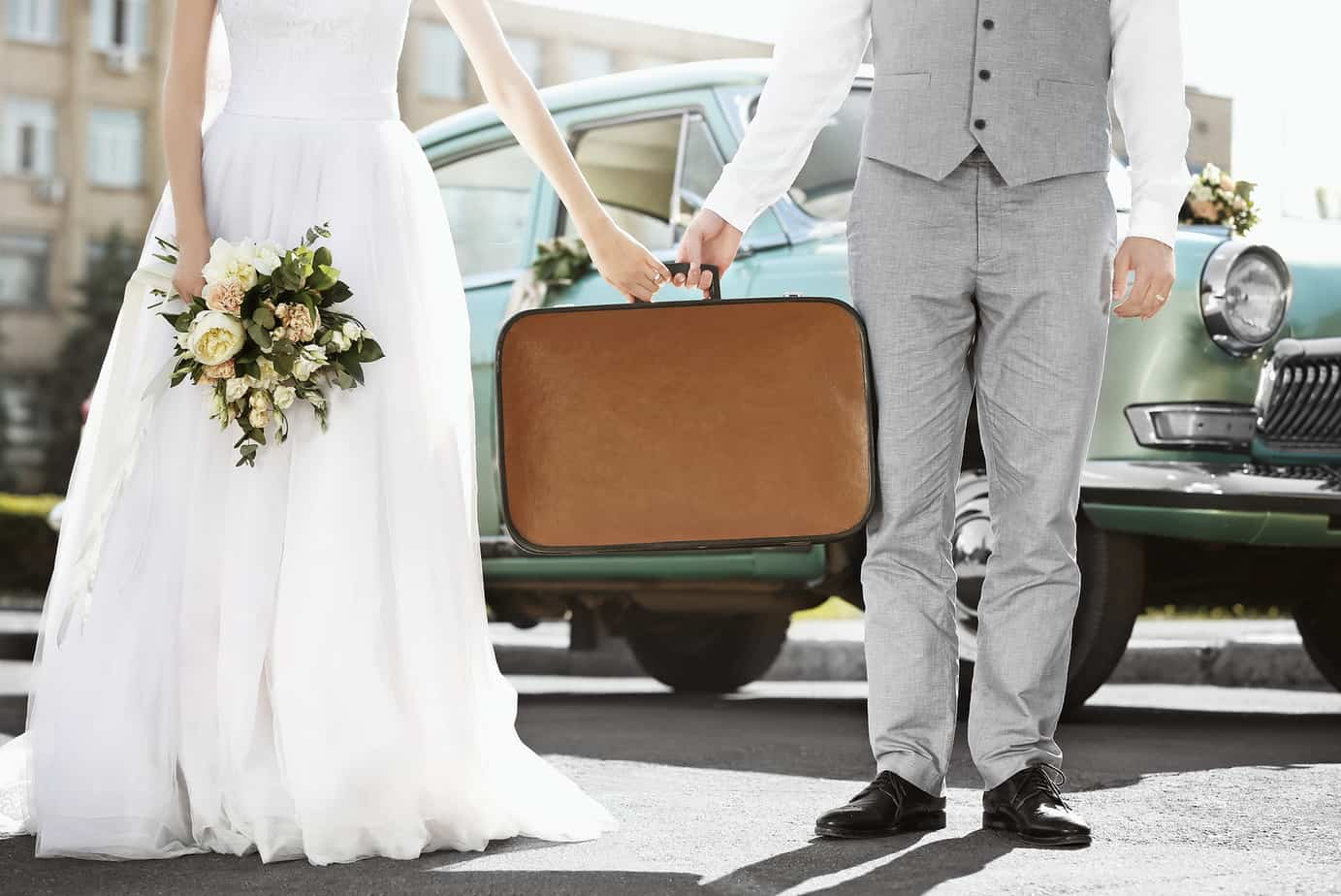 how to plan a travel themed wedding - Happy wedding couple with suitcase and car outdoors