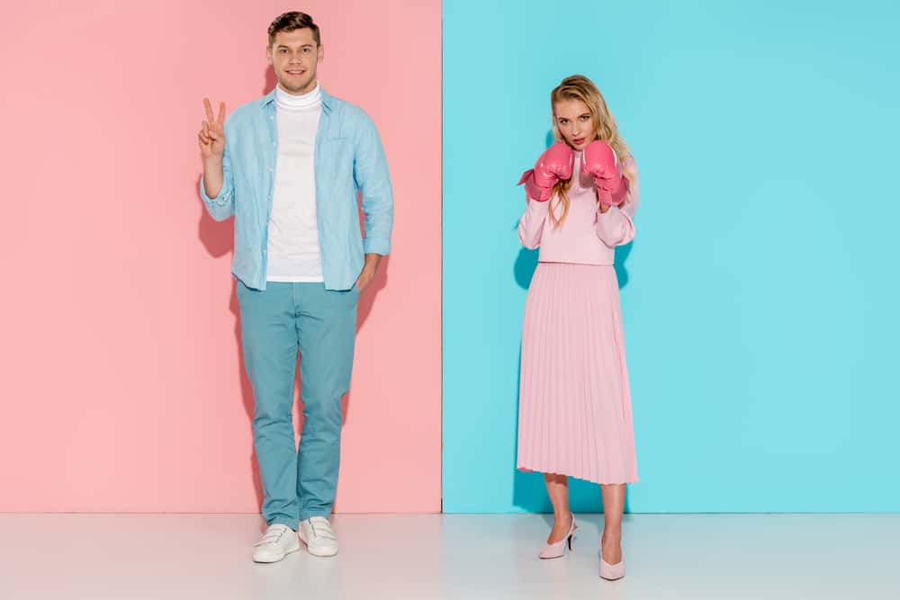 fair fighting rules for couples - man and woman in blue and pink clothes standing against opposite color backgrounds, woman wears pink boxing gloves, man is giving peace sign