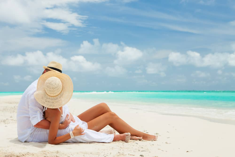 romantic beach getaways in usa - couple sitting on white sandy beach near turquoise water, they are laying together and looking away from the camera. both wear sun hats