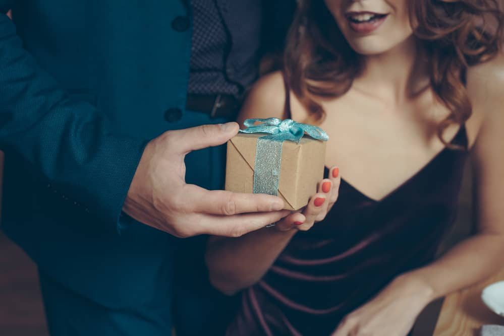 paper anniversary gifts - image of man giving woman a small gift wrapped in brown paper with a blue ribbon. their heads are out of the frame and we see just hands and the female torso