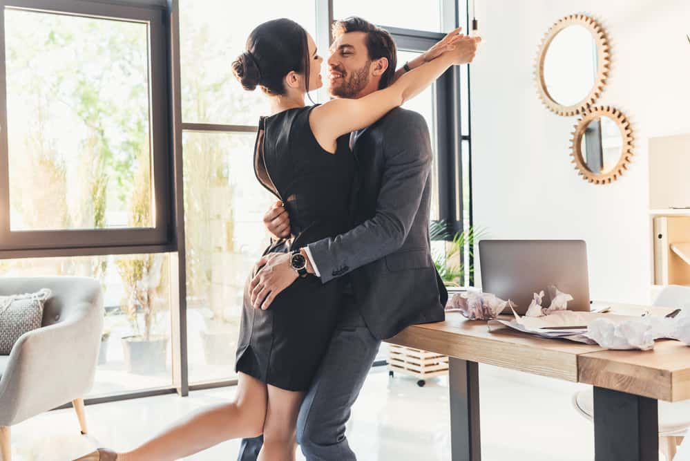 how to flirt with your husband - man and woman embracing playfully in an office setting