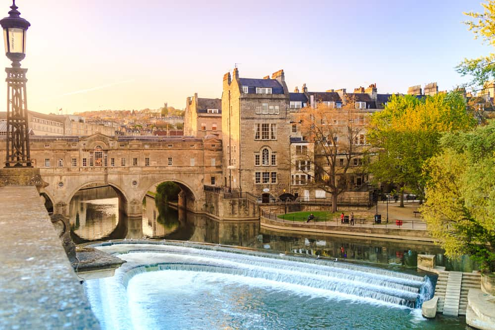 romantic things to do in bath uk - image of sun setting over classic bridge in Bath UK, lampost and rippling water are seen