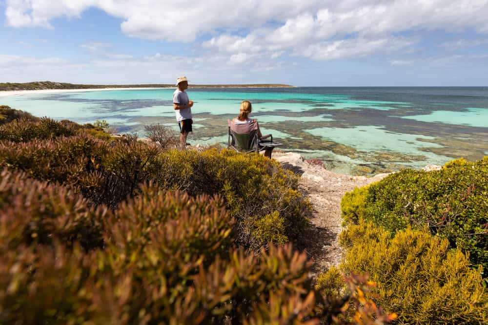 romantic things to do in south australia - couple sitting on camping chairs overlooking turquoise sea in south australia