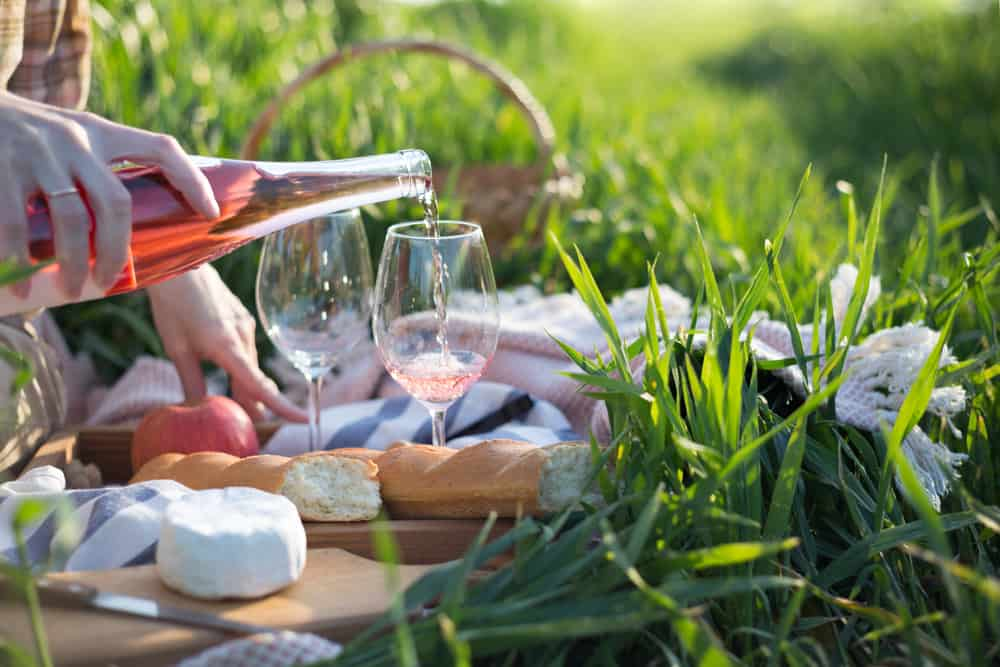 romantic things to do in provence france - image of picnic set up in green grass, rose wine being poured. cheese sits on charcuterie board