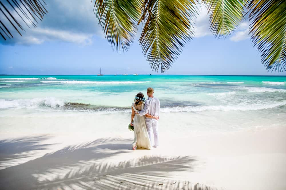 romantic things to do in punta cana - image of couple in wedding gear standing on white sand beach framed by gentle green palm trees