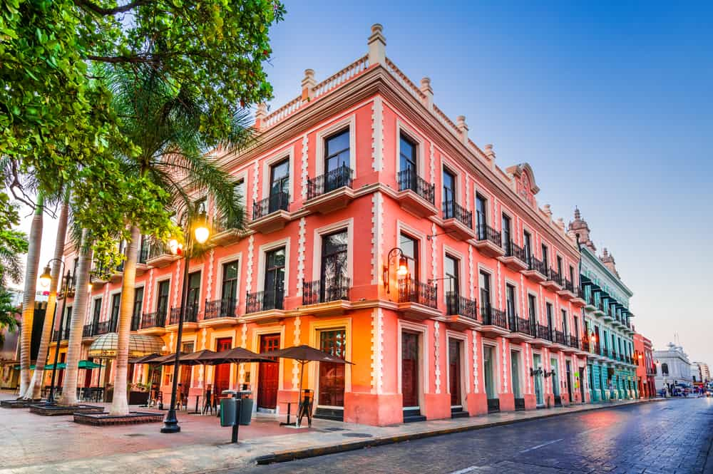 pink hued colonial building in mexico, bright colors, under a blue sky - header image things to do in merida mexico