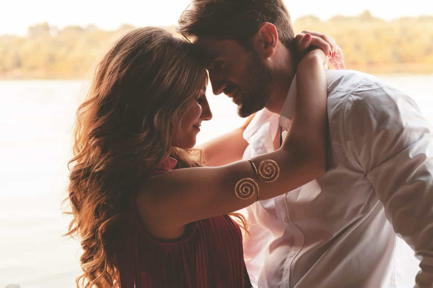 spice up your marriage - image of attractive couple embracing at sunset, woman has arms around man's neck and their foreheads are touching
