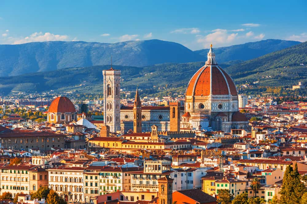romantic things to do in florence - iconic image looking over the Italian city of Florence. the orange topped Duomo is visible and mountains in the distance