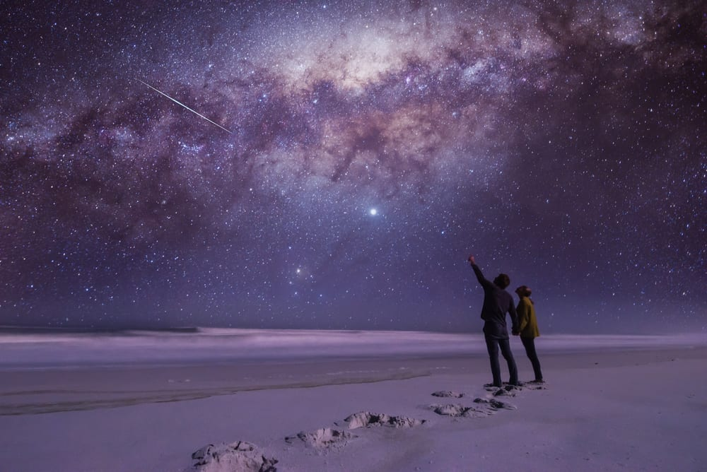 couple stargazing in a beautiful open spot with a blue and purple milkway above them