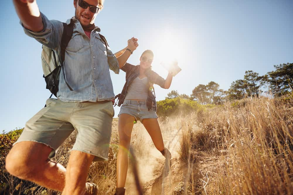 Portrait of happy young couple having fun on their hiking trip, sliding down the mountain trail. Caucasian hiker couple
