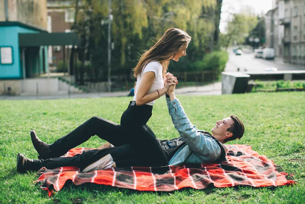 couple playing romantically on a blanket in a grassy field